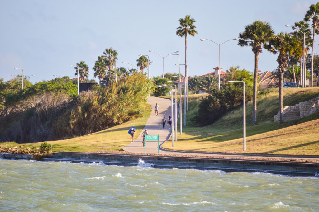 People out exercising and enjoying a late evening along the seashore in Corpus Christi, Texas in October.